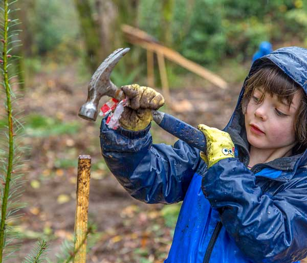 Photo of a young community member participating in a Port of Seattle-sponsored tree planting event.